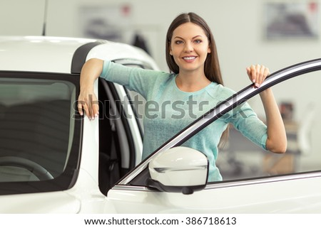 Beautiful young woman in casual clothes is smiling and looking at camera while leaning on a new car in a motor show
