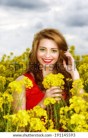 Beautiful young  woman in red dress in yellow field