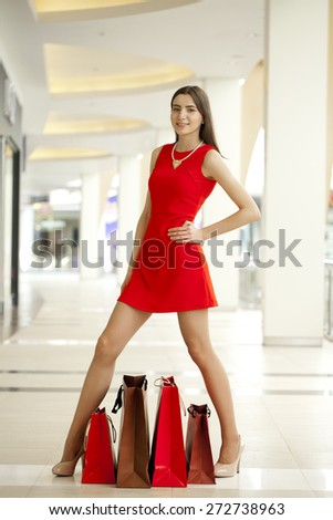 Beautiful young woman in red sexy dress in the shop
