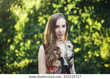 Beautiful young woman in summer garden, bright evening light