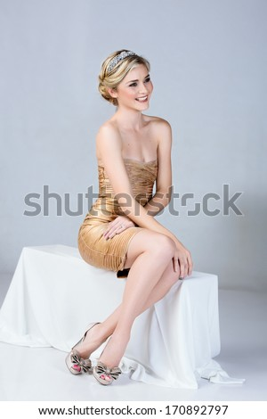 Beautiful young woman in tight gold mini dress sitting on studio background