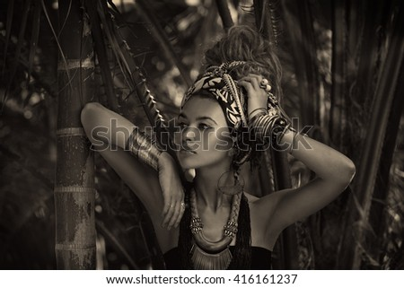 beautiful young woman in turban with jungle background. Black and white portrait