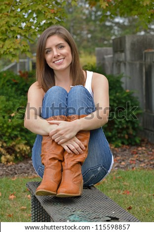Beautiful young woman in white tank, blue jeans and boots sitting on a metal bench