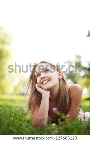 Beautiful young woman lie on grass