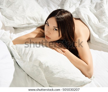 Beautiful young woman lying in the bed under the blanket. Sexy girl on white clean linens