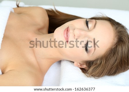 Beautiful young woman on massage table in cosmetic salon close up