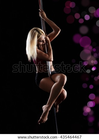 Beautiful young woman pole dancer on black background.
