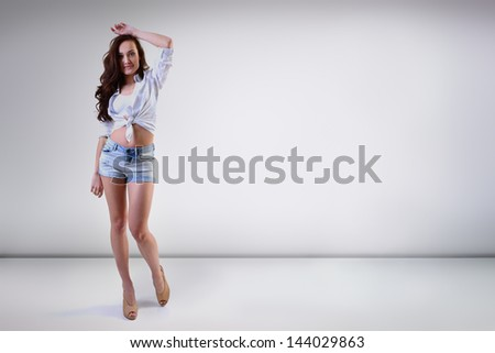 Beautiful young woman posing at studio in summer clothing, full length portrait