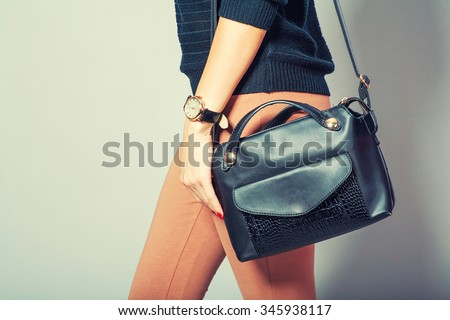 beautiful young woman posing with handbag and copy space.