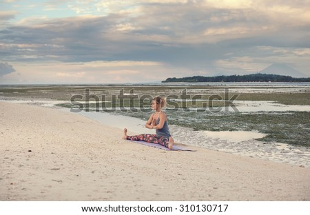 beautiful young woman practicing yoga on the beach at sunrise