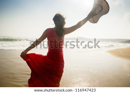 Beautiful young woman raises her hat on a sunny beach