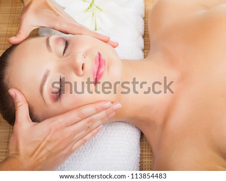 Beautiful young woman receiving massage of head in beauty salon