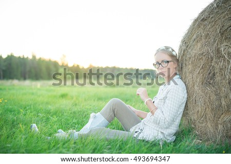 Beautiful young woman sitting on the grass in the field