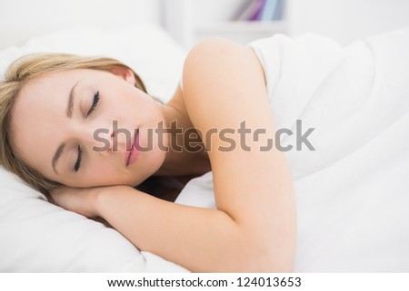 Beautiful young woman sleeping in bed at home