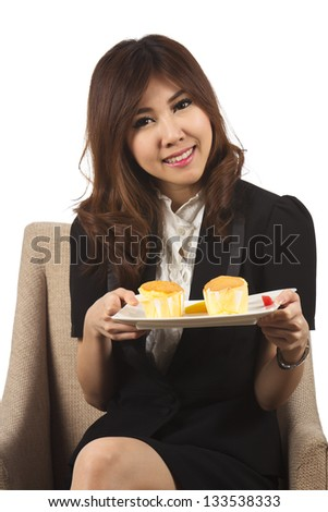 Beautiful young woman smiling with hands on the cake.