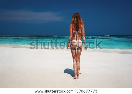 beautiful young woman standing with his back on a beautiful tropical beach with crystal clear water. Similan Islands, Thailand