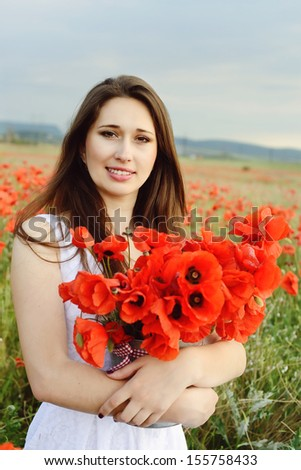 Beautiful young woman staying in field of flowers