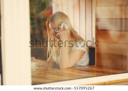 Beautiful young woman talking by mobile phone while sitting in cafe, view from outside
