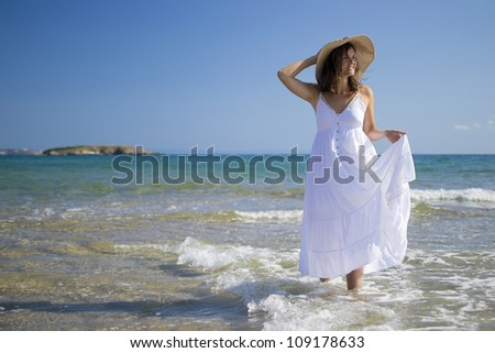 Beautiful young woman wearing a hat and a white dress playing with the waves of the sea