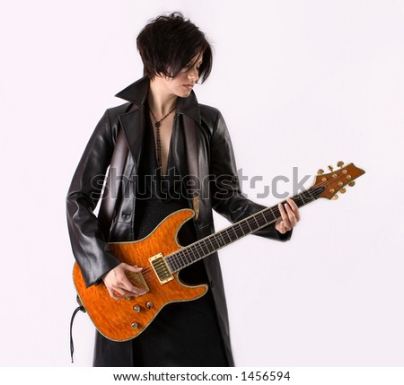 Beautiful young woman wearing leather playing guitar