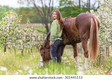Beautiful young woman with a horse in apple orchard.
