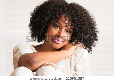 Beautiful young woman with afro in studio