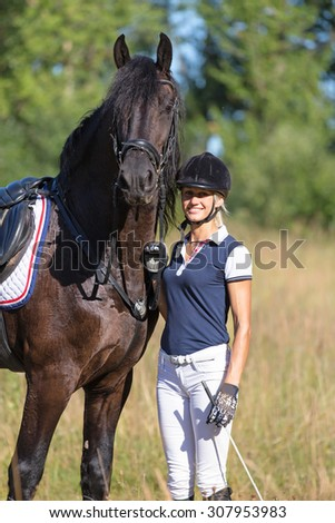 Beautiful young woman with black stallion.