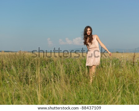 beautiful young woman with flowers in her hair standing in green field, smiling at the camera