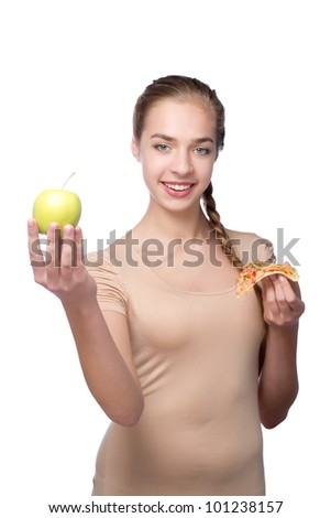 Beautiful young woman with piece of pizza and green apple on her hands