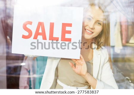 Beautiful young woman with sale announcement looking at camera from shop window