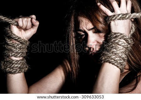 Beautiful young woman with tied arms over black background