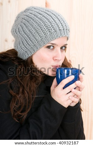 beautiful young woman with winter clothes and cup of coffee