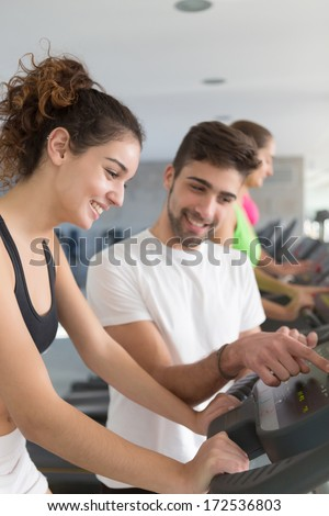 Beautiful young woman working out at the gym with the help of her personal trainer