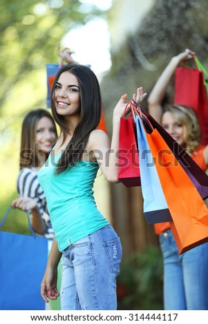 Beautiful young women with shopping bags on city street