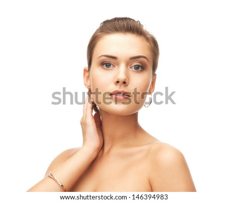 beauty and jewelry concept - beautiful woman wearing gold earrings and bracelet