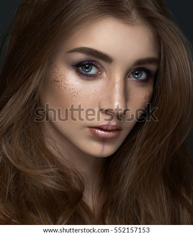 Beauty and makeup theme: portrait of a beautiful young girl model on a dark background in the studio with hair and freckles