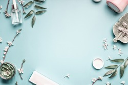 Beauty Background With Facial Cosmetic Products Leaves And Cherry Blossom On Pastel Blue Desktop