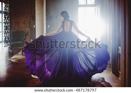 Beauty Brunette model woman in evening purple dress. Beautiful fashion luxury makeup and hairstyle