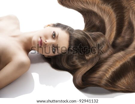 beauty close-up portrait of beautiful female face with long dark waved hairs laying down on the white. she is in front of the camera, looks in to the lens with happy expression