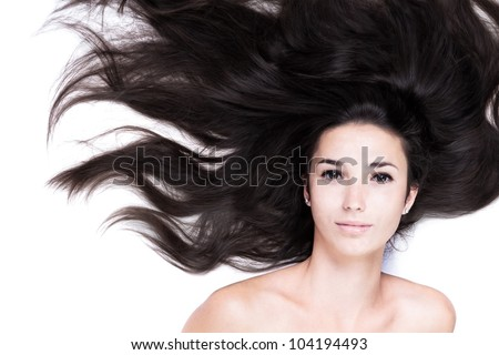 beauty close-up portrait of female face with long dark waved hairs laying down on the white. Her voluminous black hair is like the waves of the sea. beautiful woman looks with happy expression.