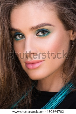 Beauty closeup portrait of beautiful young woman with wet hair and professional makeup. Necklace on her neck. Stylish in appearance