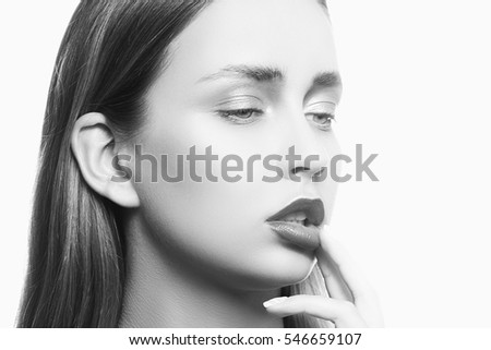 Beauty face of young girl with maroon lipstick and hand near lips isolated on white background. Studio portrait. Black and white