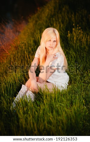 Beauty Girl Outdoors enjoying nature. Beautiful Teenage Model girl in white dress sitting on green grass on the river bank at sunset. gorgeous bride enjoying walking in spring forest.