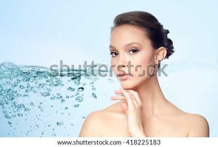 beauty, jewelry, accessories, people and luxury concept - face of beautiful young asian woman with golden ring over blue background and air bubbles in water