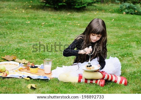 Beauty kid girl with long brunette hairs has picnic in the garden with apple pie and milk