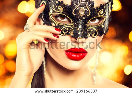 Beauty model woman wearing venetian masquerade carnival mask at party, over holiday dark background. Christmas and New Year celebration. Sexy girl with holiday makeup and manicure. Red lips and nails