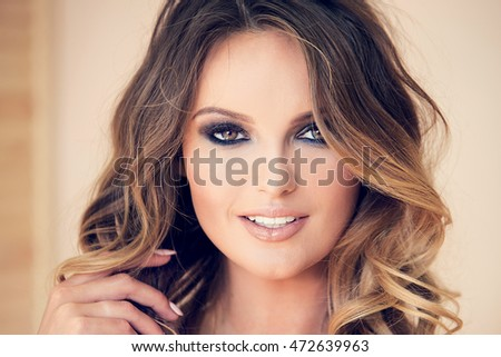 Beauty natural portrait of attractive young blonde woman with long curly hair and glamour makeup. Girl looking at camera, smiling.