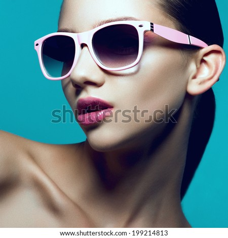 Beauty portrait of a beautiful young girl in studio with sunglasses on a blue background, close up