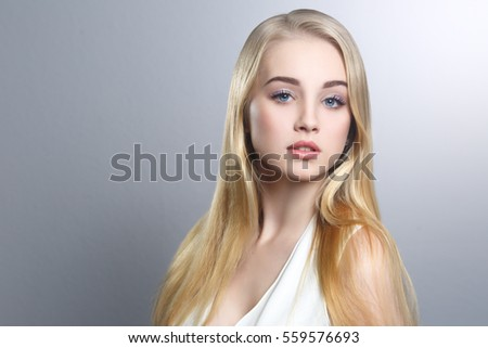 Beauty portrait of a cute blonde with long straight hair isolated groomed on a gray background.