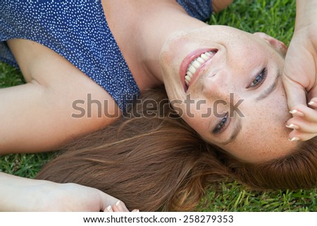 Beauty portrait of an attractive young beautiful tourist woman laying down on green grass in a park, relaxing on a summer holiday, smiling. Healthy living, beauty and well being lifestyle, exterior.